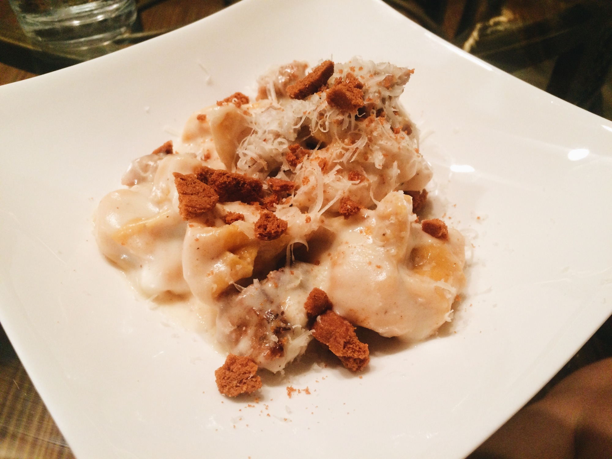 Pumpkin Sacchetti Pasta with crumbled sausage and a bechamel sauce with crumbled amaretti
